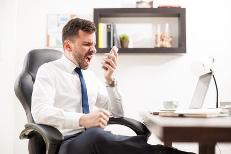 Photo for Profile view of a furious businessman yelling to a phone while seating in front of his desk in an office - Royalty Free Image