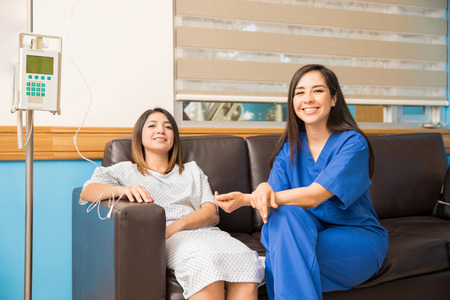 Photo for Portrait of a beautiful nurse sitting with one of her recovering patients in a hospital room and smiling - Royalty Free Image