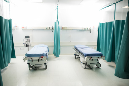 Wide view of a couple of empty beds in an emergency room at a hospital