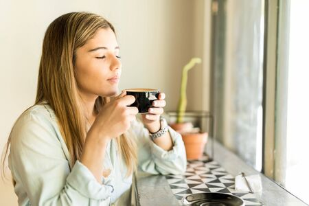 Photo pour Profile view of a beautiful young woman drinking some coffee and enjoying its aroma - image libre de droit