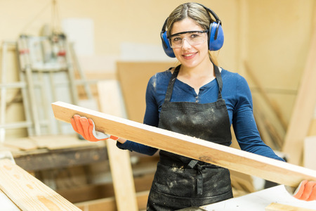 Cute young female carpenter cutting some wood in a table saw and enjoying her work