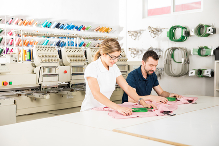 Photo pour Wide view of two people getting some garments ready for embroidery in a textile factory - image libre de droit