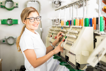 Photo pour Profile view of a cute female worker setting up some thread rolls in an embroidery machine at a factory - image libre de droit