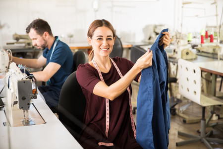Photo pour Portrait of a beautiful Hispanic female tailor holding a garment while sitting in front of a sewing machine - image libre de droit