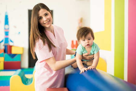 Portrait of a gorgeous Hispanic therapist doing some early stimulation exercises with a baby