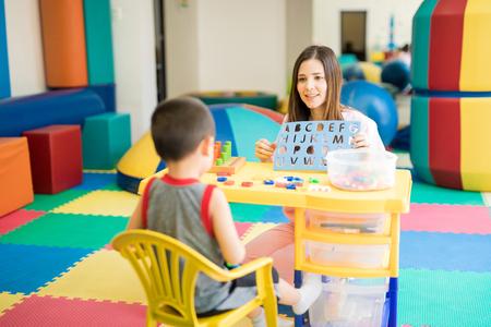 Photo pour Good looking female language therapist working with a boy in a rehabilitation center - image libre de droit