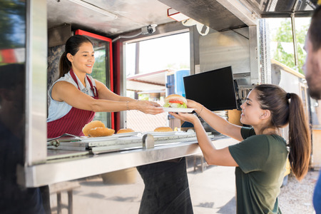 Photo pour Profile view of a food truck worker handing over a hamburger to a customer and smiling - image libre de droit