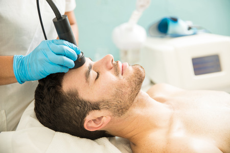 Photo pour Profile view of a good looking young man getting a RF facial treatment in a health spa - image libre de droit