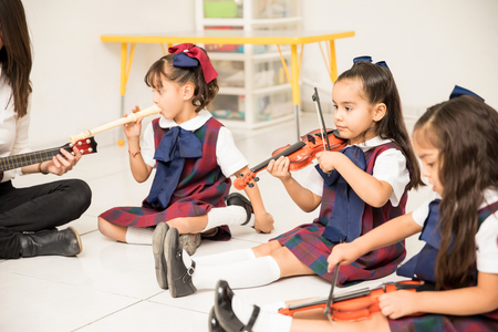Photo pour Pretty Latin girls in a preschool class learning some music with their teacher - image libre de droit