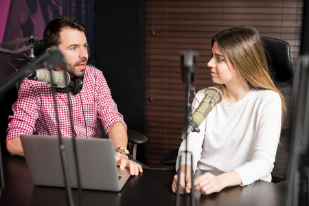 Photo pour Portrait of male radio presenter interviewing a woman guest in a radio studio for a podcast - image libre de droit