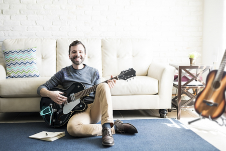 Smiling male music composer sitting on floor with a book and guitar