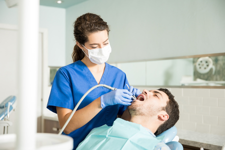 Female dentist treating mid adult male patient with dental equipment in clinic