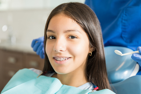 Photo for Close-up portrait of smiling teenage girl with braces against dentist standing in clinic - Royalty Free Image