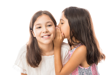 Photo pour Portrait of two little girls sharing secrets whispering to each other ear while enjoying time together - image libre de droit