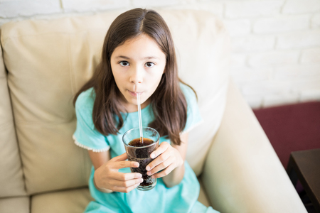 Portrait of a cute young girl enjoying soda drink at home with straw sitting on couchの写真素材