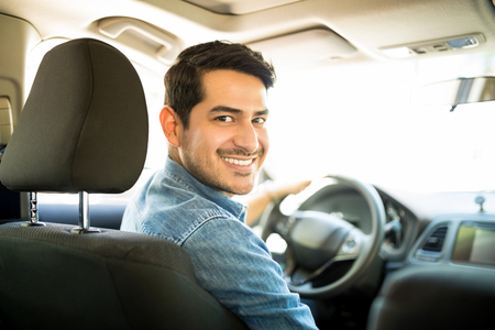 Foto de Portrait of good looking young hispanic man sitting in the driving seat of the car and looking back with a smiling face - Imagen libre de derechos