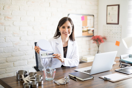 Photo pour Portrait of attractive nutritionist sitting at her clinic holding weight scale with measuring spoon set and bowl on table - image libre de droit