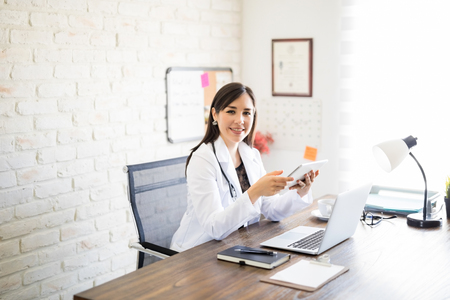 Photo pour Portrait of beautiful hispanic female doctor sitting at her clinic with a digital tablet making an eye contact - image libre de droit
