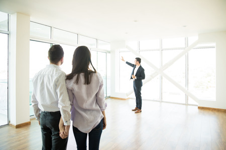 Photo pour Couple holding hands while looking at estate agent showing window of new apartment - image libre de droit