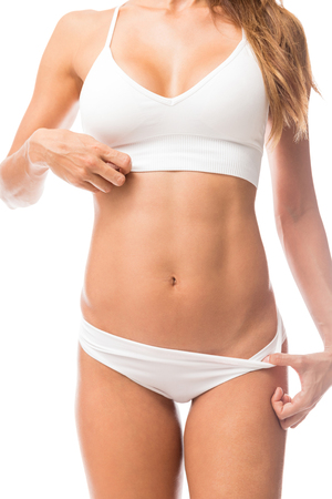 Photo for Cropped active woman proudly displaying her toned abs in studio - Royalty Free Image
