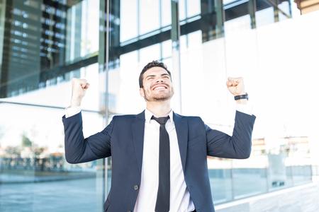 Photo pour Good looking businessman clenching fists in triumph outside modern office - image libre de droit