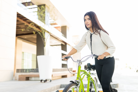 Female office worker getting on bike to reach office in city