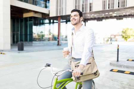 Young professional taking a break from riding bicycle on city street