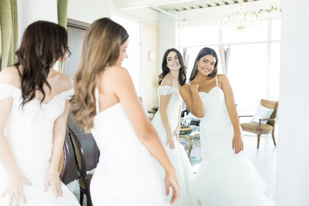Foto de Cute young brides in white dresses looking into mirror at wedding boutique - Imagen libre de derechos