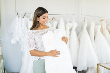 Foto de Cute Hispanic woman choosing white wedding outfit in bridal shop - Imagen libre de derechos