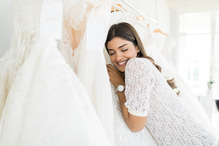 Foto de Beautiful Hispanic woman with eyes closed hugging her marriage gown in bridal shop - Imagen libre de derechos