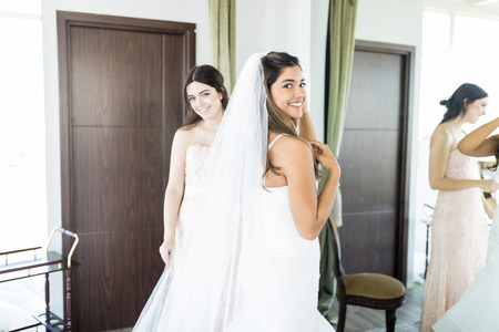 Foto de Gorgeous bride in white luxury dress is getting ready for wedding with friend in living room - Imagen libre de derechos