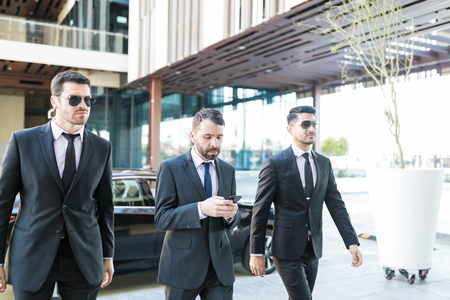 Photo for Personal bodyguards in suits protecting president while walking at campus - Royalty Free Image