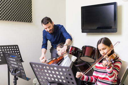 Photo pour Mid adult man assisting boy in playing violin at music class - image libre de droit