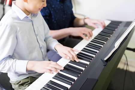 Photo pour Midsection of boy learning to play electric piano from teacher in music class - image libre de droit