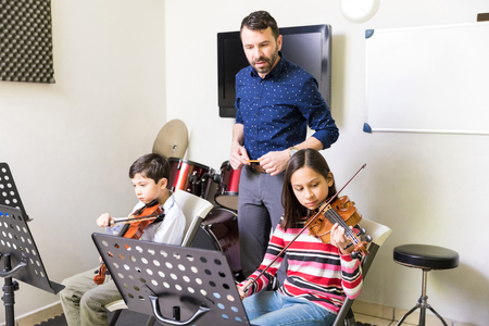 Photo pour Professional teacher listening to music played by cute students in classroom - image libre de droit
