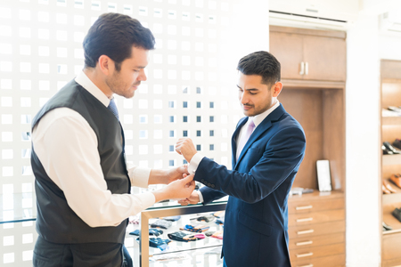 Seller assisting fashionable businessman to try out cufflinks in rental store