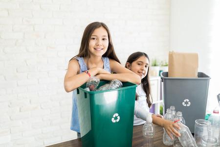 Photo pour Portrait of confident preteen girl gathering bottles with sister at home - image libre de droit
