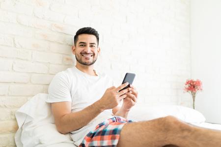 Foto de Portrait of attractive man installing new app on smartphone in bedroom - Imagen libre de derechos