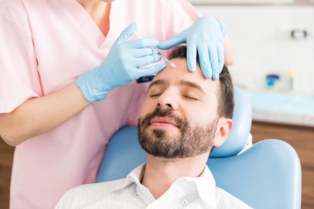 Foto für Calm male patient receiving wrinkle smoothing injection by surgeon in clinic - Lizenzfreies Bild