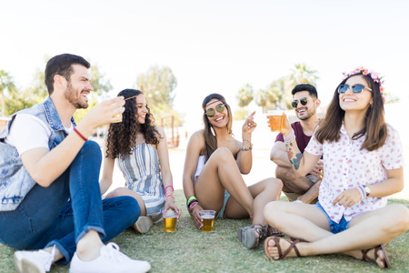 Photo pour Cheerful trendy male and female friends enjoying drinks together on field at music festival - image libre de droit