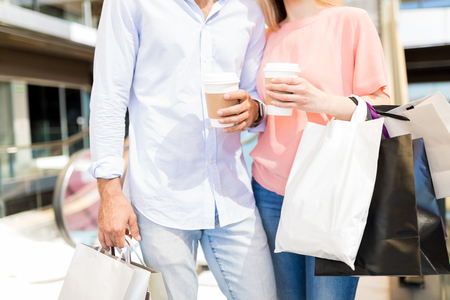 Photo for Midsection of young man and woman with disposable coffee cups and bags in shopping mall - Royalty Free Image