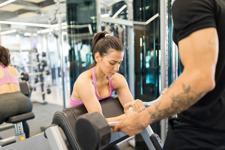 Photo for Focused young woman training with the help of personal trainer in health club - Royalty Free Image