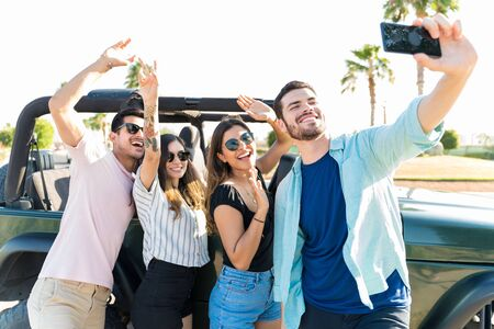 Photo pour Young man taking selfie with happy friends by SUV in summer vacation - image libre de droit