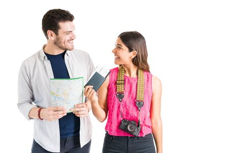 Photo for Cheerful young tourists holding map and passport while standing against plain background - Royalty Free Image