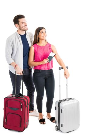 Photo pour Beautiful woman holding passport while standing by handsome boyfriend with luggage in studio - image libre de droit