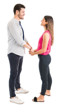 Photo for Loving young man and woman looking at each other while holding hands over plain background - Royalty Free Image