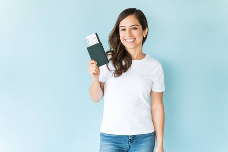 Photo pour Happy pretty female tourist with passport isolated on colored background - image libre de droit