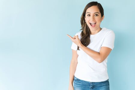 Photo for Surprised beautiful brunette pointing at empty space on isolated background - Royalty Free Image