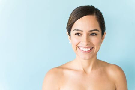 Photo for Beautiful shirtless female with flawless skin smiling over colored background - Royalty Free Image