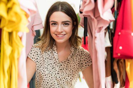 Photo pour Pretty Caucasian woman enjoying shopping while peeking through tops hanging at store - image libre de droit